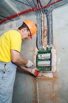 電気技師はスイッチングヒューズボックスに電線をインストールします。