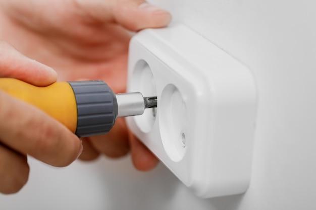 ドライバーで壁に電気ソケットをインストールする電気技師。閉じる