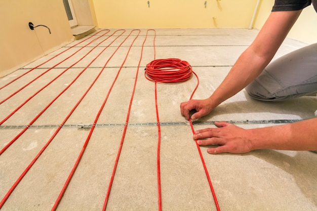 Electrician installing heating red electrical cable wire on cement floor in unfinished room.