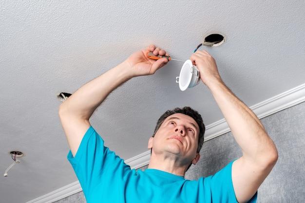 천장에 led 스포트라이트를 설치하는 전기 기사