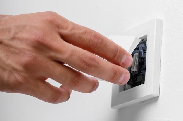 Электрик, устанавливающий выключатель света на стене. закрыть