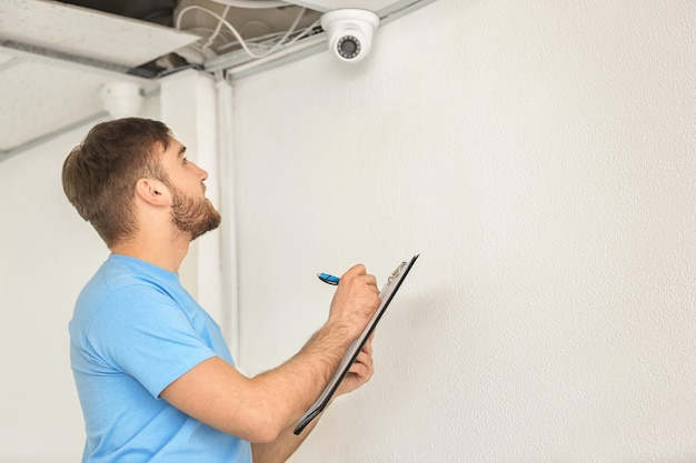 Electrician installing security camera indoors