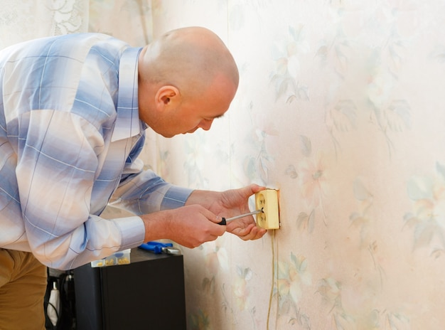 집에 벽면 소켓을 설치하는 전기 기사