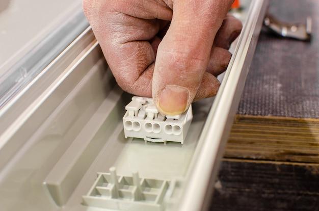 電気技師は天井の蛍光灯を設置します。修理とメンテナンスのコンセプト。電気コネクタの接続。