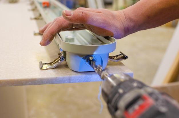 電気技師は新しい天井蛍光灯を設置します。修理とサービスのコンセプト。ワイヤー用の穴を開けます。
