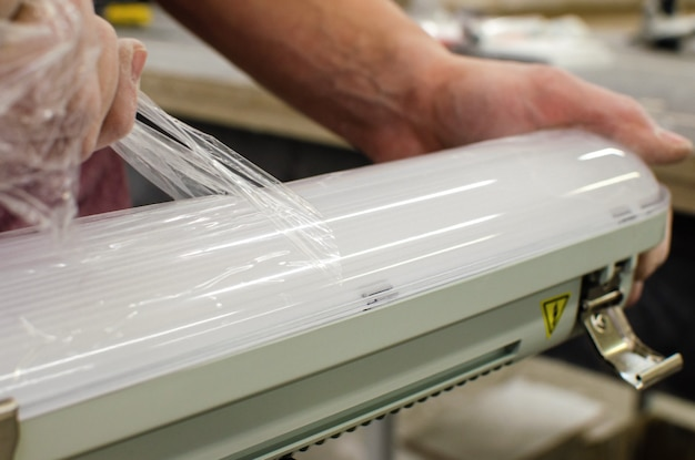 電気技師は新しい天井蛍光灯を設置します。修理とサービスのコンセプト。保護フィルムの取り外し。