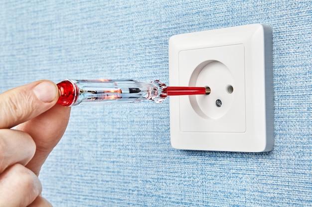 Электрик вставляет тестер-отвертку с одним контактом и красной светодиодной лампой в отверстие розетки для определения фазного провода.