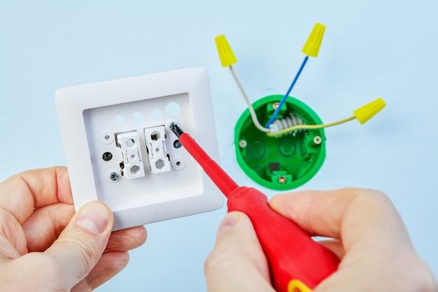 Электрик устанавливает новый двойной выключатель света.