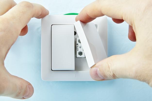 전기 기사는 새로운 버튼을 만드는 새로운 유럽 표준 전등 스위치를 설치하고 있습니다.