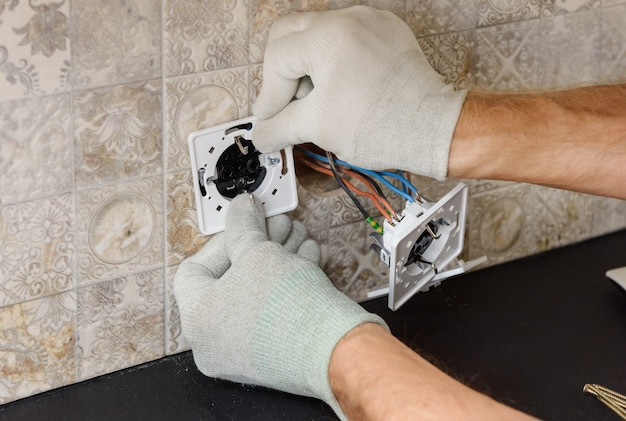 An electrician is installing switches and sockets on the wall.