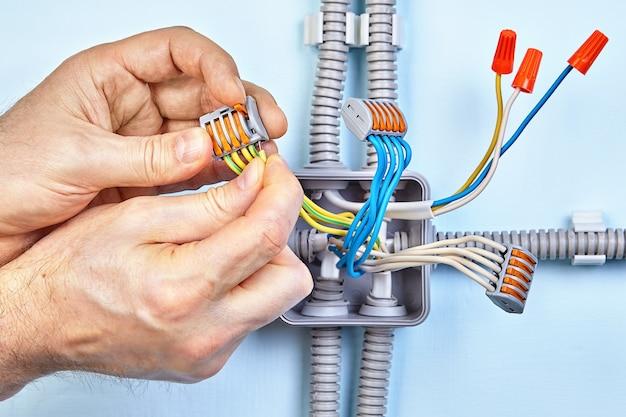 Electrician은 푸시 와이어 커넥터를 사용하여 전선 용 새 정션 박스를 만들고 있습니다.