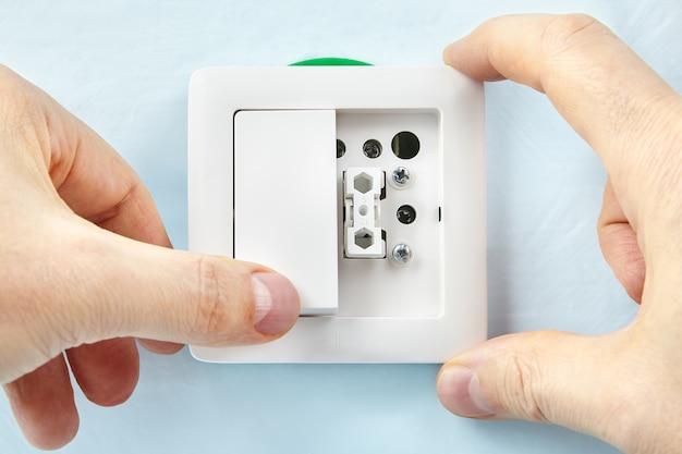 전기 기사가 새 버튼을 켜는 새 전등 스위치를 만들고 있습니다.