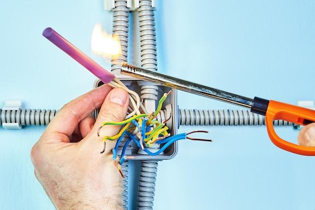 電気技師は、ジャンクションボックスの絶縁ツイストワイヤ用の火熱収縮チューブを設定しています。