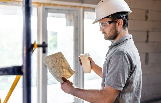 An electrician is studying a construction drawing with a coffee in his hand.