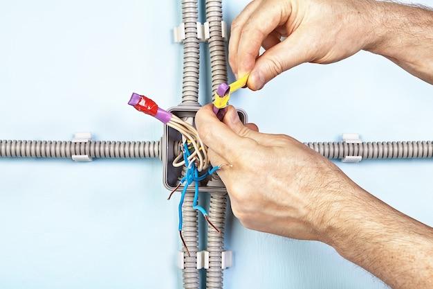 電気技師は、ジャンクションボックスの取り付け中に、熱収縮性チューブのワイヤの端をテーピングしています。