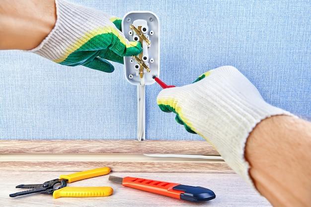 電気技師は、ドライバー、電気サービスで新しい壁のコンセントのネジを締めています。
