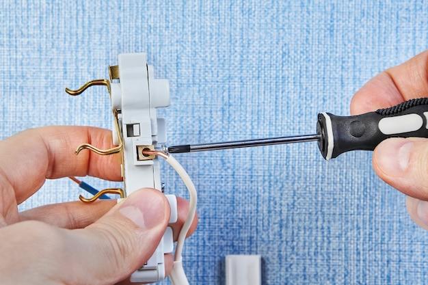 電気技師は新しいコンセントのネジをねじっています。
