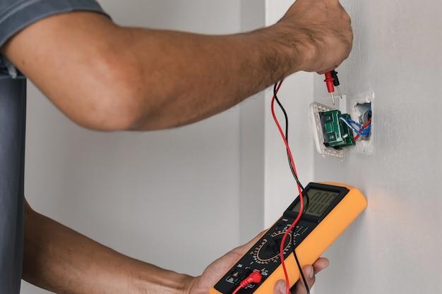 Электрик использует цифровой измерительный прибор для измерения напряжения на электрической розетке