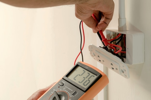 Electrician is using a digital meter to measure the voltage at the power outlet.