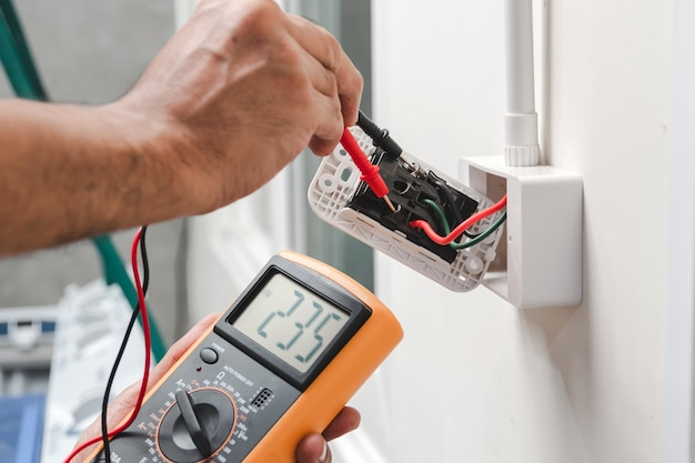 Electrician is using a digital meter to measure the voltage at the power outlet in on the