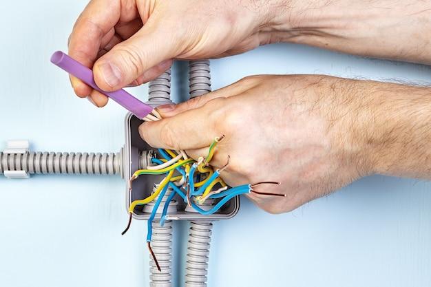 電気技師は、ワイヤーの端を結合するために熱収縮チューブを使用して、良好な接触を実現しています。
