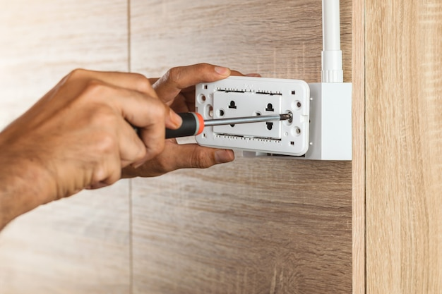 Electrician is using a screwdriver to install the electric power socket in to a plastic outlet box on a wooden wall.