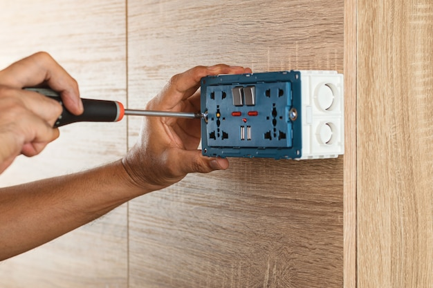 Electrician is using a screwdriver to install a power outlet in to a plastic box on a wooden wall.