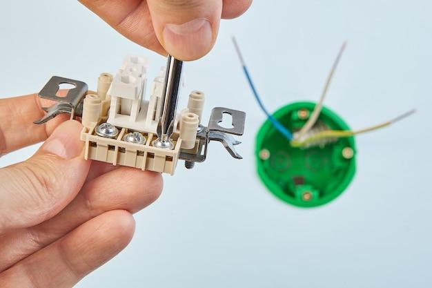 전기 기사는 드라이버, 전기 설치 작업의 도움으로 새로운 이중 전등 스위치로 작업하고 있습니다.