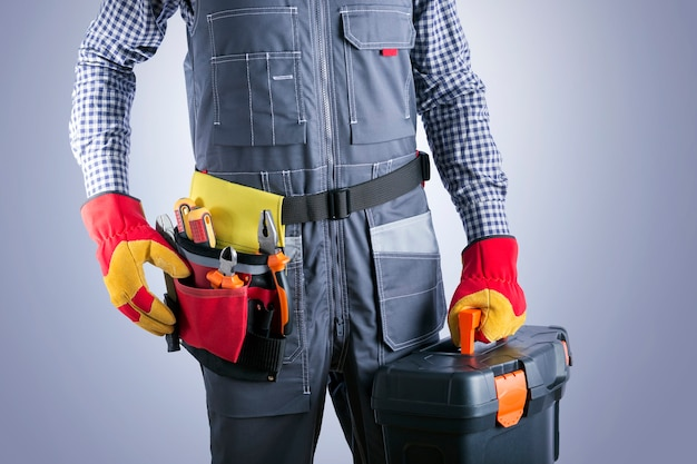 Electrician in jumpsuit with toolbox against gray surface. repair and renovation service.