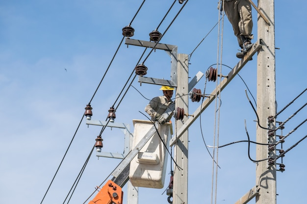 Electrician on the lifts working to repair power lines