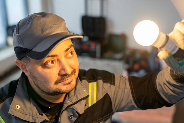 Электрик смотрит на включенную лампочку, свет от которой освещает его лицо