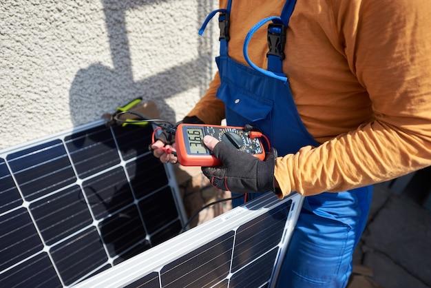 現代の家の屋根にソーラーパネルを取り付ける電気技師