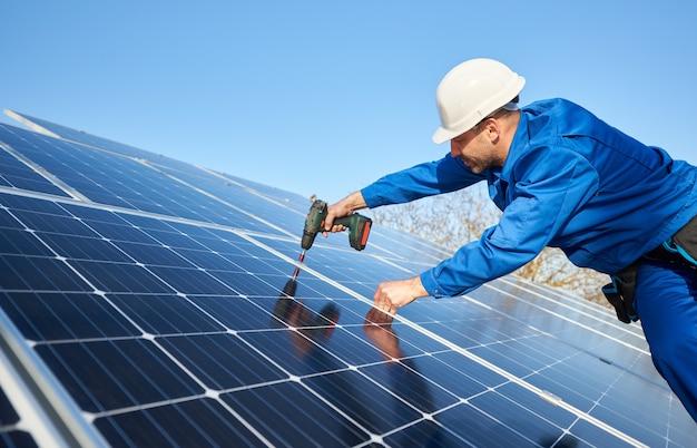 Electrician mounting solar panel on roof of modern house