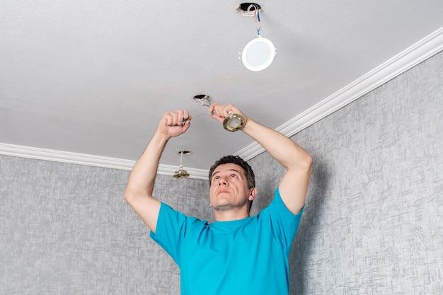 전기 기사가 천장에서 오래되고 비효율적 인 할로겐 램프를 제거합니다.