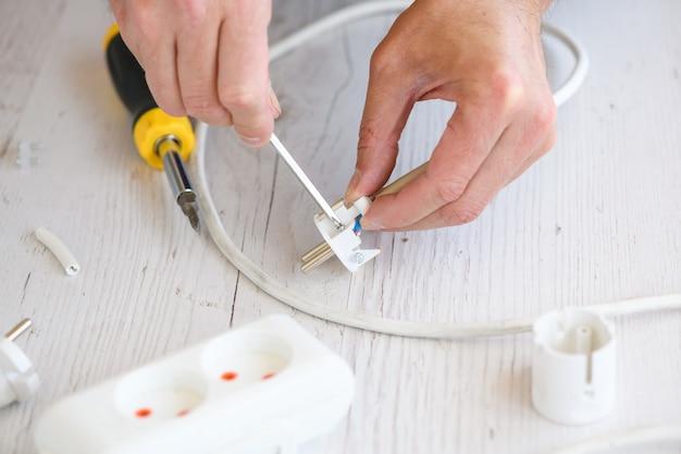Электрик-ремонтник руки крутит и затягивает винты с помощью отвертки на небольшом пластиковом европейском удлинительном шнуре, удлинитель крупным планом