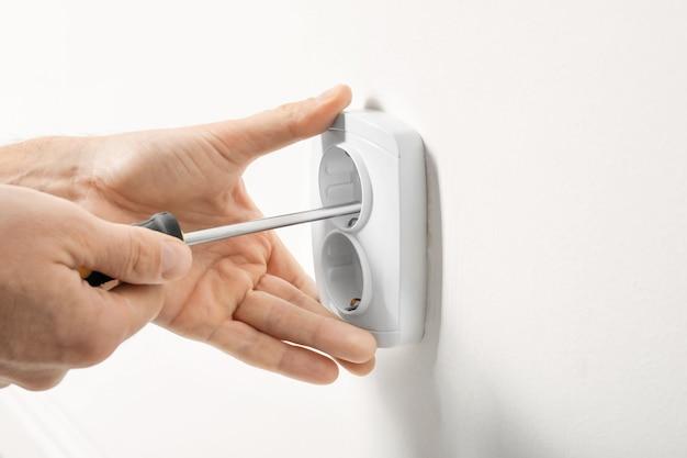 軽い壁のソケットを修理する電気技師 Premium写真