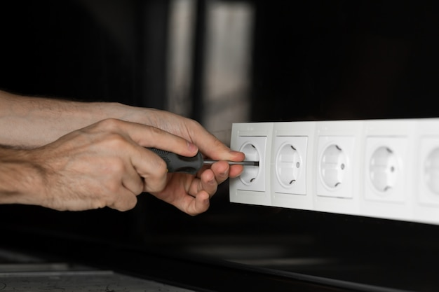 검은 유리 벽에 흰색 전기 콘센트를 분해하는 드라이버로 전기의 손.