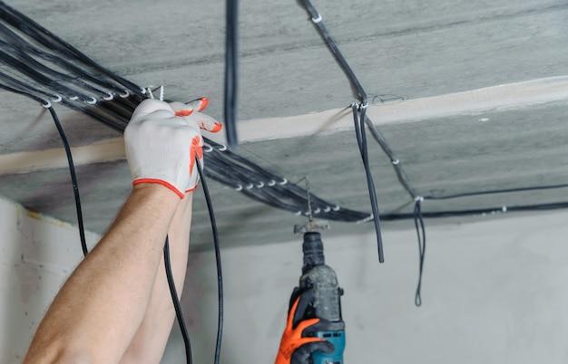 전기 기사의 손이 천장에 전기 케이블을 고정하고 있습니다.