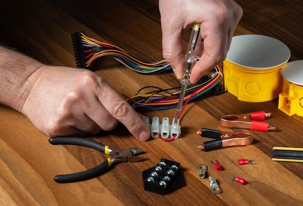 電気技師はドライバーでワイヤーをコネクターにねじ込みます。マスターの手のクローズアップ