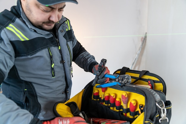 An electrician in special clothes carefully examines contents of tool bag