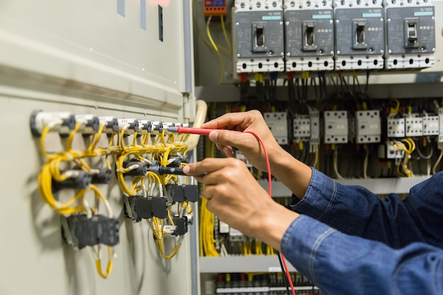 Electrician   tester measuring  voltage and current in electical cabinet control