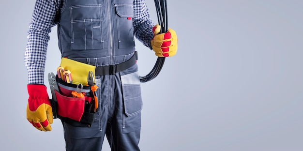 Electrician in uniform with wires and tools on  grey surface with copy space. banner.
