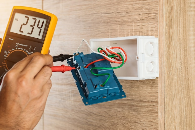 Electrician using a digital meter to measure the voltage at a wall socket on a wooden wall.