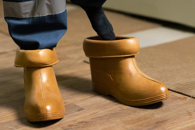 Electrician wears rubber boots electrical technician is putting on special protective shoes