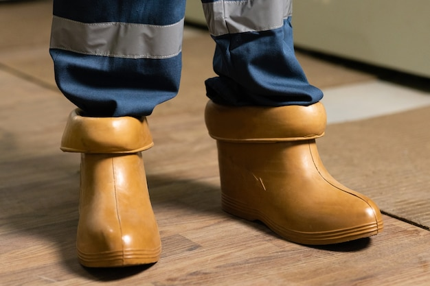 Electrician wears rubber boots for safety to avoid electric shock concept of electric power station
