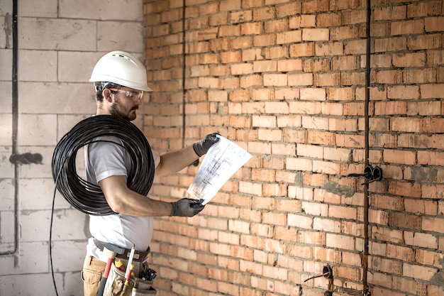 Электрик со строительными инструментами, глядя на чертежи на строительной площадке