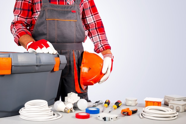 Electrician with electrical equipment and tools against grey wall with copy space.