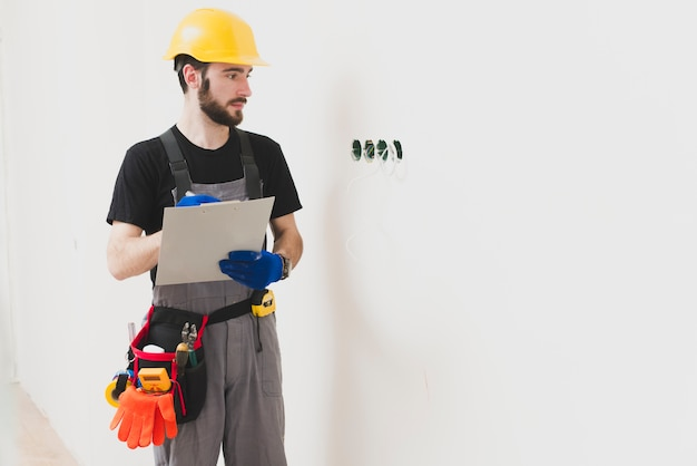 Electrician with paper tablet looking at holes