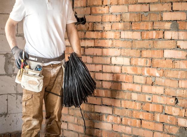 Электрик с инструментами, работает на строительной площадке. концепция ремонта и разнорабочего.