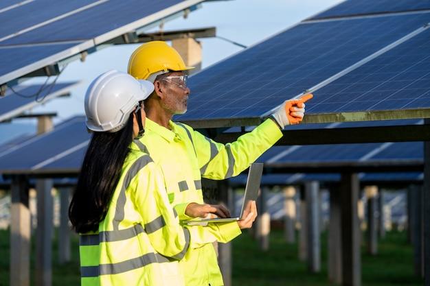 반사 조끼와 안전모를 쓰고 태양 전지판에서 일하고 새로운 태양 전지판 설치에 대해 이야기하는 전기 기사.